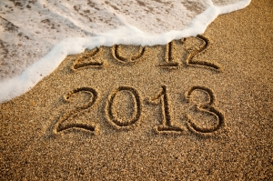 Wave erasing 2012 written on the sand with 2013 on foreground